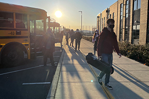 lakewood high school students step off the school bus with masks on